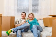 Photo of man and woman with wine glasses with wine sitting on sofa among cardboard boxes. Photo of men and women with wine glasses with wine sitting on sofa stock photo