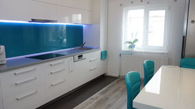 Photo of mid size kitchen apartment in turquoise colours, leather modern and minimalist seater, white dining table for six persons Stock Photos