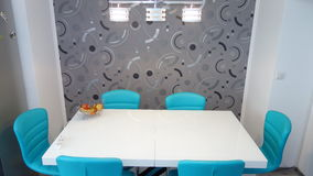 Photo of mid size kitchen apartment in turquoise colours, leather modern and minimalist seater, white dining table for six persons Royalty Free Stock Photos