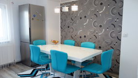 Photo of mid size kitchen apartment in turquoise colours, leather modern and minimalist seater, white dining table for six persons Royalty Free Stock Photo