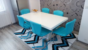 Photo of mid size kitchen apartment in turquoise colours, leather modern and minimalist seater, white dining table for six persons Royalty Free Stock Image