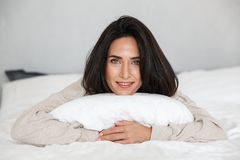 Photo of middle-aged woman 30s smiling, while lying in bed with white linen at home stock photo