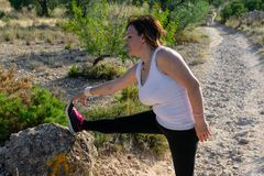 Photo of middle aged woman in sports clothes practicing stretching outdoor royalty free stock photos