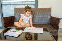 Photo mignonne de peinture de petite fille sur le fond int?rieur ? la maison Gar?on et filles s'asseyant sur le bureau surfant et images libres de droits