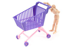Photo with miniature shopping-cart and wooden man Royalty Free Stock Photo