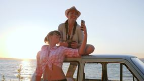 Photo at mobile of Beautiful Friends near automobile on shore river, Lovely girls Photographed near vehicle stock video