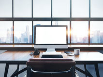 Photo of modern workspace with panoramic windows. Photo of generic design computer screen and workspace in loft with panoramic windows and city on the background Stock Photos