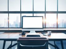 Photo of modern workspace with panoramic windows. Photo of generic design computer screen and workspace in loft with panoramic windows and city on the background Royalty Free Stock Image