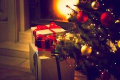 Photo modifiée la tonalité d'arbre de Noël et boîte-cadeau contre le sapin brûlant Images libres de droits