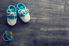 Photo modifiée la tonalité des petits chaussons à crochet bleus d'enfant avec peu de mamelon o Photographie stock libre de droits