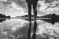 Photo monochrome des jambes femelles marchant sur l'eau avec le reflec de ciel Images stock