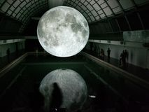 Photo of Moon Hologram Floating on Water Near People Inside Room Stock Image