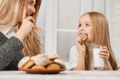 Photo of mother and daughter eating cookies and smile. royalty free stock photos