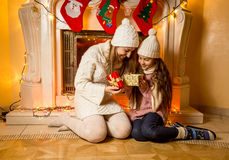 Photo of mother and daughter sitting at fireplace with Christmas Royalty Free Stock Photo