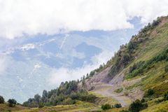 Photo of mountain slopes with vegetation and cloudy sky Stock Images