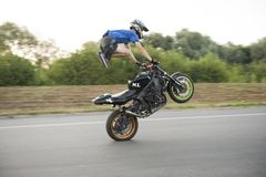 Photo of moving brave biker standing on motorcycle during riding. Stock Photos