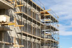 Photo of multistory high rise building with scaffolding. Side view photo of wall unfinished house with iron elements on scaffolding stock photo