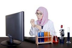 Muslim female scientist working on desk Stock Photo