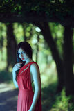 Photo of mystical sexy woman in red dress in fairy forest. Beauty springtime. Wonderful sexy fashion model walking in a fantastical forest by footpath.Mystical Royalty Free Stock Images