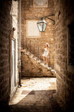 Photo on narrow street of young woman standing on stone stairs Stock Images