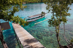 Photo Natural Wood Long Tail Boat Parked Caribbean Ocean Pier. Clear blue water. Horizontal. Royalty Free Stock Photos