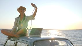 Photo at nature in sunlight, girl sits on roof retro car in backlight makes selfie on phone, young woman using powered stock footage