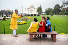 Photo near Taj Mahal. AGRA, UTTAR PRADESH, INDIA - FEBUARY 24, 2015: Indian family taking group picture with foreign in red dress on the bench in the garden Royalty Free Stock Images