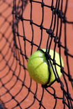 Photo of new tennis ball struck in net. Photo of new tennis ball struck in tenis net on a clay court Royalty Free Stock Photo