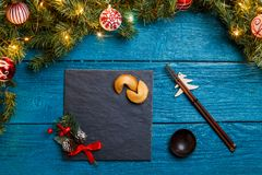 Photo of New Year branches of fir, black board, sticks for sushi, cookies with prediction. On blue wooden background Royalty Free Stock Photos