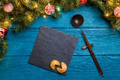 Photo of New Year branches of fir, black board, sticks for sushi, cookies with prediction. On blue wooden background Stock Images