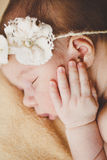 Photo of a newborn baby curled up sleeping on a blanket Stock Photos