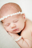 Photo of a newborn baby curled up sleeping on a blanket Stock Photo