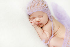 Photo of a newborn baby curled up sleeping on a blanket Stock Image