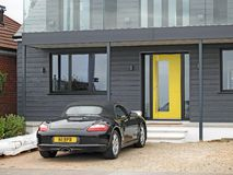 Luxury living new homes. Photo of a newly build modern home with black wooden panelled facia and yellow door with expensive porsche car in drive royalty free stock photography
