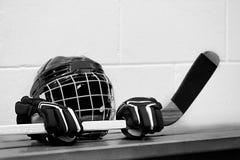 Photo noire et blanche d'équipement d'hockey sur le banc : Casque, gants et bâton Image libre de droits