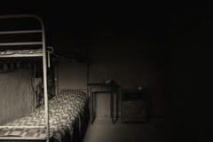 Photo noire et blanche de cellule de prison vide foncée avec la couchette de fer image stock