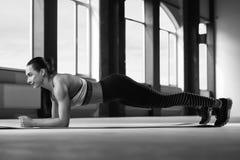 Photo noire et blanche de femme sportive avec le corps fort faisant la planche images stock