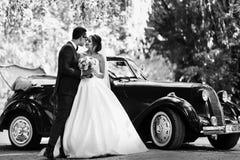 Photo noire et blanche des deux à côté d'une voiture Images libres de droits