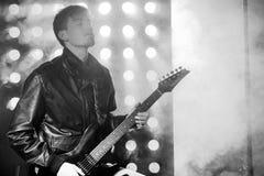 Photo noire et blanche du jeune musicien de roche jouant la guitare électrique et le chant Vedette du rock sur le fond des projec Photo libre de droits