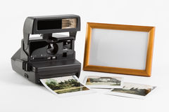Photo Nostalgie of 90s. «Still life» of retro/old-fashioned instant camera with instant photographies and blank frame on white background Stock Photography