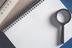 Photo of notebook to spiral into the cell lying on the table with a magnifying glass and a wooden ruler Royalty Free Stock Photo