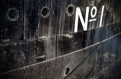 Photo of a number one sign on a grungy ship side. Stock Photos