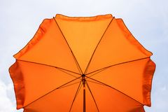Free Photo Of A Beach Umbrella On The Blue Sky,Beach Umbrella.One Vibrant Orange Colored Sunshade Against Vivid Blue Sky And White Stock Photography - 152133482