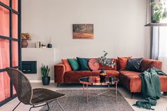 Free Photo Of A Comfy Living Room Interior With A Round Table On Gray Rug, Wicker Armchair And Red Corner Sofa Stock Images - 165389784