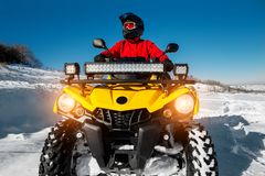 Free Photo Of Attractive Young Man In Red Warm Winter Clothes And Black Helmet On The ATV 4wd Quad Bike Stand In Heavy Snow Royalty Free Stock Images - 139752159