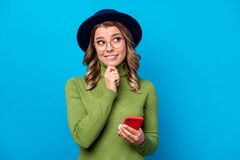 Free Photo Of Cheerful Curly Lady Hold Telephone Blogger Think Over New Creative Post Look Up Empty Space Biting Lips Wear Royalty Free Stock Images - 181692789
