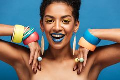 Photo Of Magnificent Half-naked Woman With Colorful Makeup Smiling And Demonstrating Accessories On Her Arms, Isolated Over Blue Royalty Free Stock Images