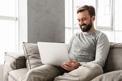 Free Photo Of Pleased Adult Man 30s In Casual Clothing Typing On Laptop, While Working In Cozy Home Stock Image - 115311481