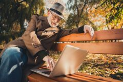 Free Photo Of Positive Old Man Rest Relax Autumn Colorful Holiday Forest City Center Park Sit Bench Use Laptop Chat Son Royalty Free Stock Photos - 195089818