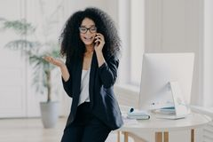 Free Photo Of Puzzled Prosperous Businesswoman Calls Partner, Raises Palm, Holds Mobile Phone, Wears Spectacles And Formal Black Outfit Stock Image - 161215881